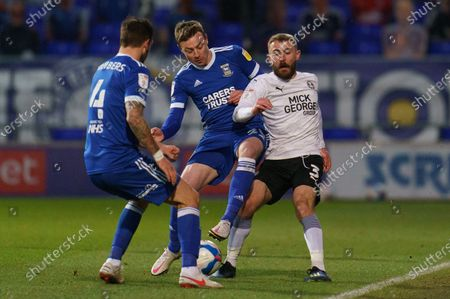 Stock Picture of Dan Butler of Peterborough United (3) is surrounded by Luke Chambers of Ipswich Town (4) and Freddie Sears of Ipswich Town (20)