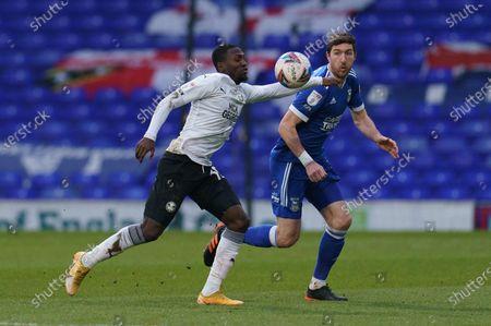 Idris Kanu of Peterborough United (19) and Stephen Ward of Ipswich Town (3)