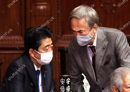 Former Japanese Prime Minister Shinzo Abe (L) chats with former Internal Affairs Minister Nobuteru Ishihara (R) at Lower House's plenary session at the National Diet in Tokyo on Wednesday, January 20, 2021. Ishihara was infected with the new coronavirus, news reported on January 22.