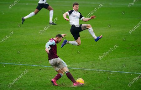 Joe Bryan of Fulham jumps to block a pass from Phil Bardsley of Burnley