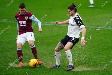 Stock Photo of Johann Gudmundsson of Burnley and Joe Bryan of Fulham play in tricky conditions