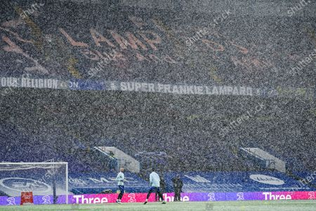 Goalkeepers Edouard Mendy and Willy Caballero of Chelsea warm up in the snow underneath the new Frank Lampard banner made by Chelsea supporters
