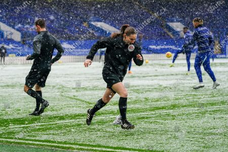 Assistant Referee Sian Massey-Ellis warms up in the heavy snow