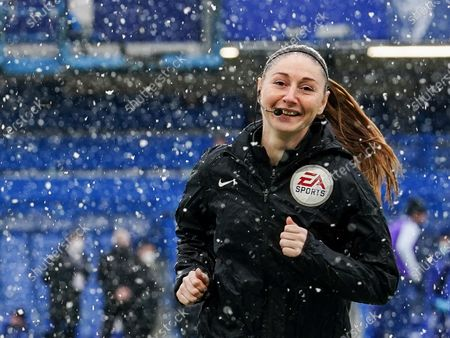 Assistant referee Sian Massey-Ellissmiles smiles as she warms up in the heavy snow
