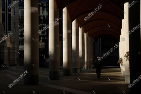 Stock Image of Man wearing a face mask to curb the spread of coronavirus walks in Paternoster Square, in the City of London financial district of London, during England's third national lockdown since the coronavirus outbreak began. The U.K. is under an indefinite national lockdown to curb the spread of the new variant, with nonessential shops, gyms and hairdressers closed, most people working from home and schools largely offering remote learning