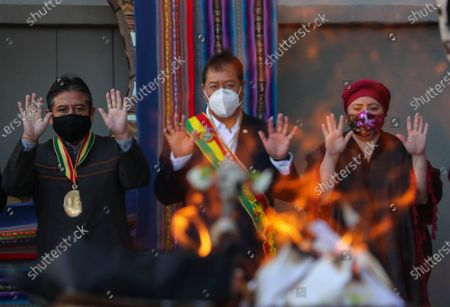 Stock Image of Bolivia's President Luis Arce (C) and Vice President David Choquehuanca (L), who also chairs the Legislative Assembly, and the Minister of the Presidency Maria Nela Prada (R) participate in an ancestral ceremony during the official ceremony for the Plurinational State Day, a holiday established eleven years ago by the Movement to Socialism (MAS), to remember the Evo Morales' first investiture in 2006, in La Paz, Bolivia, 22 January 2021. The celebration of the Day of the Plurinational State in Bolivia began with an indigenous ritual of gratitude to the 'Pachamama' or Mother Earth.