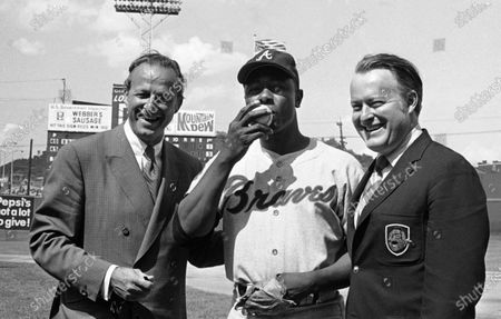 Atlanta Braves' Hank Aaron, center, poses for photos after getting his 3,000th career hits during a baseball game against the Cincinnati Reds in Cincinnati. At left is Hall of Famer Stan Musial who was the last man to accomplish the feat, hitting his 3,000th in 1958. At right is Bill Bartholomay, owner of the Braves. Hank Aaron, who endured racist threats with stoic dignity during his pursuit of Babe Ruth but went on to break the career home run record in the pre-steroids era, died early . He was 86. The Atlanta Braves said Aaron died peacefully in his sleep. No cause of death was given