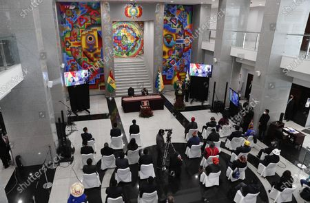 """Bolivia's President Luis Arce, standing at the podium at right, addresses the nation at the presidential palace in La Paz, Bolivia, . The message marked the anniversary of the naming of Bolivia as the """"Plurinational State of Bolivia,"""" by former President Evo Morales"""