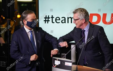 Stock Image of Armin Laschet (L), new party leader of the German Christian Democrats (CDU), taps elbows with CDU election commissioner Thomas De Maiziere after a count of ballots confirmed Laschet's election at CDU headquarters on January 22, 2021 in Berlin, Germany. Laschet was the preliminarily declared victor at the digital CDU party congress a week ago and today's count of the approximately 1,000 delegate ballots have made the result official.