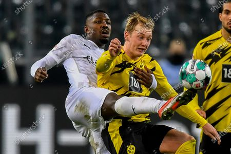 Moenchengladbach's Marcus Thuram, left, duels for the ball with Dortmund's Julian Brandt during the German Bundesliga soccer match between Borussia Moenchengladbach and Borussia Dortmund in Moenchengladbach, Germany