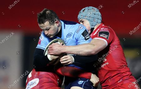 Hallam Amos of Cardiff Blues is tackled by Steff Evans and Jonathan Davies of Scarlets.