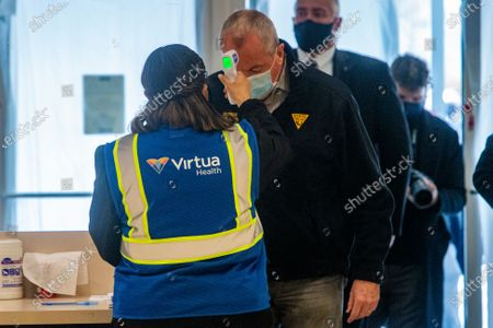 New Jersey Governor Phil Murphy gets his temperature taken as he enters the Burlington County COVID-19 Vaccination Mega-Site in the former Lord and Taylor at Moorestown Mall, Friday morning, in Moorestown, N.J. He along with other local dignitaries took a tour of the facility