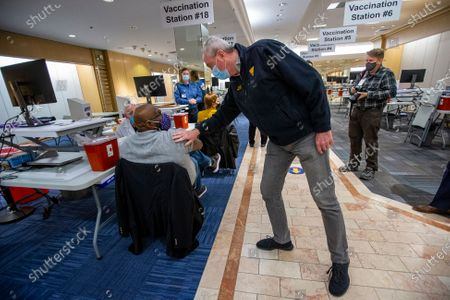 New Jersey Governor Phil Murphy greets Sen. Troy Singleton, D-Moorestown, as he waits to get vaccinated for COVID-19, in Moorestown, N.J. Murphy toured the Burlington County COVID-19 Vaccination Mega-Site inside the former Lord and Taylor at Moorestown Mall on Friday morning