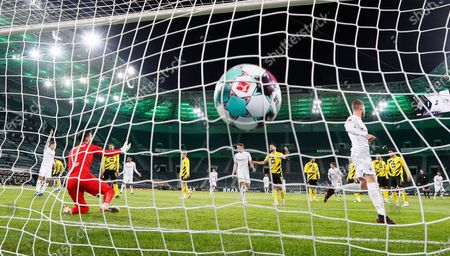Moenchengladbach's Nico Elvedi, right, scores his second goal against Dortmund's goalkeeper Roman Buerki, left, during the German Bundesliga soccer match between Borussia Moenchengladbach and Borussia Dortmund in Moenchengladbach, Germany