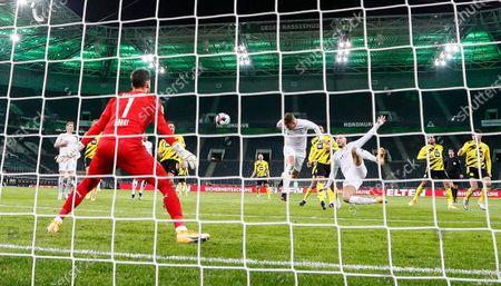 Moenchengladbach's Nico Elvedi, center, scores his first goal against Dortmund's goalkeeper Roman Buerki during the German Bundesliga soccer match between Borussia Moenchengladbach and Borussia Dortmund in Moenchengladbach, Germany