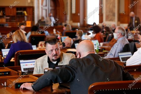 Kansas state Rep. Bill Sutton, left, R-Gardner, confers with Rep. Adam Thomas, right, R-Olathe, as the House debates a proposed anti-abortion amendment to the Kansas Constitution, at the Statehouse in Topeka, Kan. The debate came on the 48th anniversary of the U.S. Supreme Court's historic 1973 Roe v. Wade decision legalizing abortion nationwide