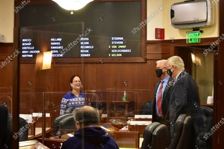 State Sen. Lora Reinbold, R-Eagle River, left, chats with Sens. Roger Holland, R-Anchorage, and Gary Stevens, R-Kodiak, before the start of the floor session of the Alaska state Senate, in Juneau, Alaska
