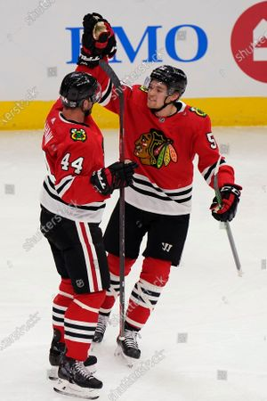 Chicago Blackhawks' Calvin de Haan, left, celebrates with Ian Mitchell after de Haan scored a goal during the second period of the team's NHL hockey game against the Detroit Red Wings in Chicago