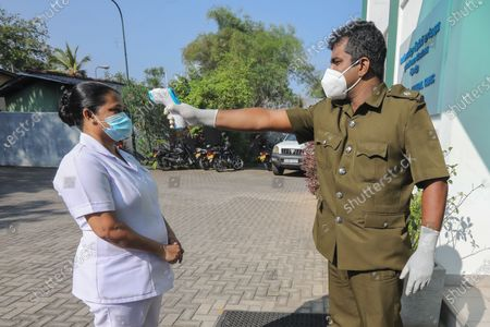 A Sri Lankan Public Health inspector carries out a body temperature check on a health worker during a mock COVID-19 vaccination procedure trial at a regional medical health office in Colombo, Sri Lanka, 23 January 2021. The mock procedure for a vaccination process was held by Sri Lanka's health authorities in three selected locations, during the trials, any problems that could arise in the drill would be identified. The trials will also be useful in deciding the number of vaccines that can be distributed within a certain timeframe, said Dr. Hemantha Herath, the Deputy Director-General of Health Services. The Sri Lankan health ministry announced on 22 January that the government had granted regulatory approval for the emergency use of the Oxford-AstraZeneca vaccine. Meanwhile, Sri Lanka's Minister of Health Ms. Pavithra Wanniarachchi has been tested positive for coronavirus disease (COVID-19).
