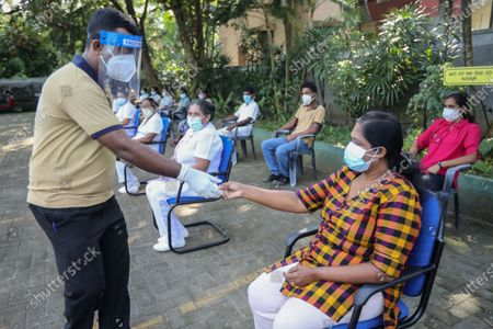 Sri Lankan health workers take part in a mock COVID-19 vaccination procedure trial at a regional medical health office in Colombo, Sri Lanka, 23 January 2021. The mock procedure for a vaccination process was held by Sri Lanka's health authorities in three selected locations, during the trials, any problems that could arise in the drill would be identified. The trials will also be useful in deciding the number of vaccines that can be distributed within a certain timeframe, said Dr. Hemantha Herath, the Deputy Director-General of Health Services. The Sri Lankan health ministry announced on 22 January that the government had granted regulatory approval for the emergency use of the Oxford-AstraZeneca vaccine. Meanwhile, Sri Lanka's Minister of Health Ms. Pavithra Wanniarachchi has been tested positive for coronavirus disease (COVID-19).