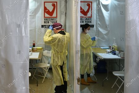 Healthcare workers prepare to receive patients at a NYCHA vaccine pop up site at the William Reid Apartments in New York.