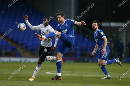 Stephen Ward of Ipswich Town clears under pressure from Idris Kanu of Peterborough United