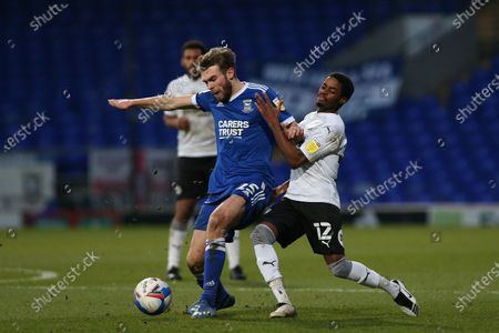 Aaron Drinan of Ipswich Town holds off a challenge from Reece Brown of Peterborough United