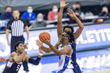 Creighton guard Denzel Mahoney (34) drive to the basket against Connecticut forward Josh Carlton (25) and Connecticut forward Isaiah Whaley (5) in the second half during an NCAA college basketball game, in Omaha, Neb