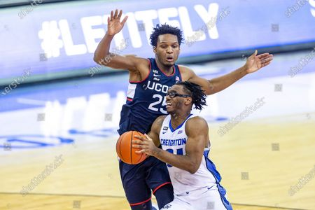 Stock Image of Creighton guard Denzel Mahoney (34) drive to the basket against Connecticut forward Josh Carlton (25) in the second half during an NCAA college basketball game, in Omaha, Neb