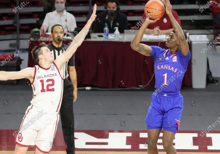 Kansas Jayhawks guard Tyon Grant-Foster (1) attempts a shotas Oklahoma Sooners guard Austin Reaves (12) attempts to block it during a basketball game between the Kansas Jayhawks and Oklahoma Sooners at Lloyd Noble Center in Norman, OK