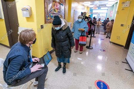 Screener registers residents of the William Reid Apartments at a COVID-19 pop-up vaccination site at the NYCHA housing complex, in the Brooklyn borough of New York