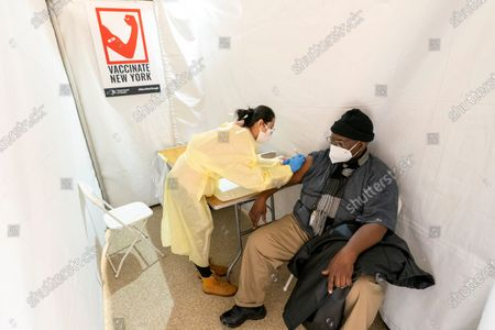 Registerd Nurse Shyun Lin, left, gives Roberto Fisher, 72, the first dose of the COVID-19 vaccine at a pop-up vaccination site in the William Reid Apartments in the Brooklyn borough of New York