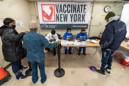 Screeners register residents of the William Reid Apartments at a COVID-19 pop-up vaccination site at the NYCHA housing complex, in the Brooklyn borough of New York