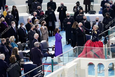 Lady Gaga sings the National Anthem during the 59th Presidential Inauguration at the U.S. Capitol in Washington, . Standing behind her are President-elect Joe Biden Vice President-elect Kamala Harris, Vice President Mike Pence and his wife Karen Pence, Chief Justice of the United States John Roberts, and Associate Justices Elena Kagan and Sonia Sotomayor and others