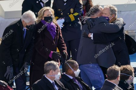 Country singer Garth Brooks hugs former President George W. Bush as former President Bill Clinton and former Secretary of State Hillary Clinton look on after Brooks performed during the 59th Presidential Inauguration at the U.S. Capitol in Washington, . Former Vice President Mike Pence is seated at left