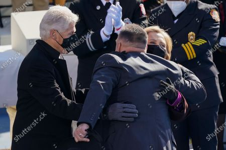 Country singer Garth Brooks hugs Former President Bill Clinton and former Secretary of State Hillary Clinton after performing during the 59th Presidential Inauguration at the U.S. Capitol in Washington, . Former Vice President Mike Pence is seated at left