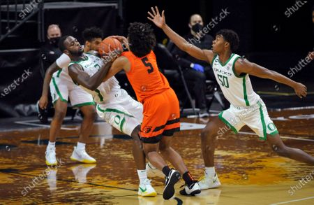 Oregon forward Eugene Omoruyi (2) fouls Oregon State guard Ethan Thompson (5) as Oregon forward Eric Williams Jr. (50) helps on defense during the second half of an NCAA college basketball game in Eugene, Ore
