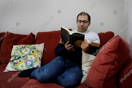 Stock Photo of Egyptian political exile and doctor by training, Mohamed Aboelgheit reads a book at his home in London, . The Jan. 25, 2011, uprising in Tahrir Square led to the quick ouster of autocrat Hosni Mubarak. A decade later, thousands are estimated to have fled abroad to escape a state, headed by Egyptian President Abdel Fattah el-Sissi, that is even more oppressive
