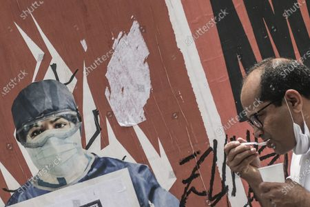 A man walks past a graffiti of a medical worker in Sao Paulo, Brazil, on Jan. 22, 2021. The Brazilian state of Sao Paulo announced on Friday a return to the strictest phase of quarantine starting on Monday, with the closure of bars, restaurants and non-essential businesses during nights and weekends due to the increase in COVID-19 cases. Governor of Sao Paulo Joao Doria said at a press conference that these measures, which will be in force until Feb. 7, are taken to avoid a collapse in the hospital system of the richest and most populated state, but also the epicenter of COVID-19 infections in Brazil.