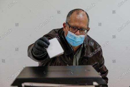 A voter casts his ballot in the presidential elections, in Lisbon, 24 January 2021. More than 10 million voters are now being asked to choose among the seven candidates for President of the Republic in elections in which abstention is the main adversary due to the covid-19 pandemic. Seven candidates are contesting the elections, Marcelo Rebelo de Sousa (current President),  Marisa Matias, Tiago Mayan Gonçalves, Andre Ventura, Vitorino Silva, Joao Ferreira and Ana Gomes.