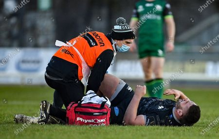 Gareth Thomas of Ospreys is tended to by medical personnel after receiving an injury