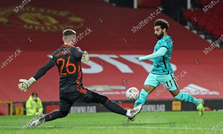 Liverpool's Mohamed Salah scores the opening goal past Manchester United's goalkeeper Dean Henderson during the English FA Cup 4th round soccer match between Manchester United and Liverpool at Old Trafford in Manchester, England
