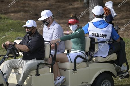 Professional baseball player Josh Donaldson and Gaby Lopez, of Mexico, wear masks while riding on a cart to the 18th hole during the final round of the Tournament of Champions LPGA golf tournament, in Lake Buena Vista, Fla
