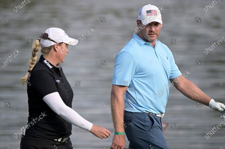 Brittany Lincicome, left, and former NFL football player Brian Urlacher chat while walking to the 17th green during the final round of the Tournament of Champions LPGA golf tournament, in Lake Buena Vista, Fla