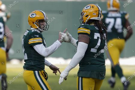 Green Bay Packers quarterback Aaron Rodgers is congratulated by teammate Billy Turner (77) after Rodgers' touchdown pass to Marquez Valdes-Scantling against the Tampa Bay Buccaneers during the first half of the NFC championship NFL football game in Green Bay, Wis