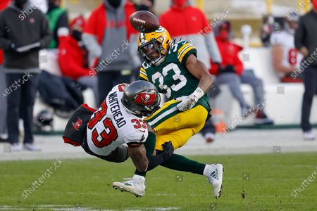 Green Bay Packers' Aaron Jones (33) fumbles after being hit by Tampa Bay Buccaneers' Jordan Whitehead (33) during the second half of the NFC championship NFL football game in Green Bay, Wis