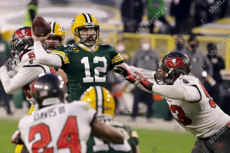 Green Bay Packers quarterback Aaron Rodgers (12) evades a tackle as he looks to pass against the Tampa Bay Buccaneers during the second half of the NFC championship NFL football game in Green Bay, Wis