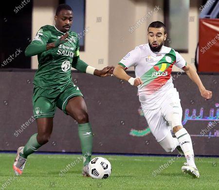 Al-Ettifaq's player Naim Sliti (R) in action against Al-Ettifaq's Motaz Hawsawi (L) during the Saudi Professional League soccer match between Al-Ettifaq and Al-Ahli at Prince Mohammed Bin Fahd Stadium, Dammam, Saudi Arabia, 24 January 2021.