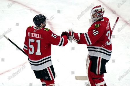 Chicago Blackhawks goalie Kevin Lankinen, right, celebrates with defender Ian Mitchell after they defeated the Detroit Red Wings in an NHL hockey game in Chicago