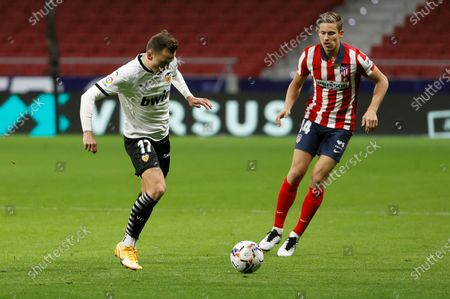 Atletico's midfielder Marcos Llorente (R) duels for the ball against Valencia's winger Denis Cheryshev (L) during the Spanish LaLiga soccer match between Atletico de Madrid and Valencia CF at Wanda Metropolitano stadium in Madrid, Spain, 24 January 2021.